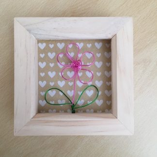 Small natural wood colour frame with a single pink wire flower against a background of beige hearts
