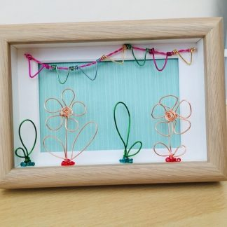 Pale wood colour box frame with copper coloured wire flowers, green wire leaves and multi-coloured wire bunting on a green background