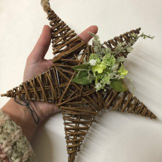 Hanging star decorated with green artificial flowers