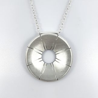Contemporary silver pendant with rays is handing on the white holder.
