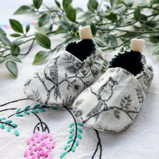 Baby shoes made in a cream linen look fabric with black vintage style birds