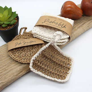 two jute kitchen scrubbies and a cotton dishcloth on a piece of wood. There is a printed paper wrap around the cream dishcloth and one of the scrubbies
