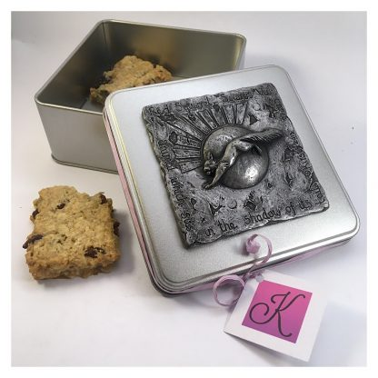 Open square tin with a red squirrel design on the lid and showing biscuits within
