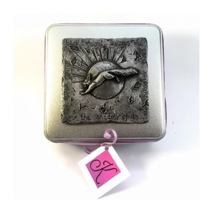 Top view of a Square tin with a raised design showing a red squirrel leaping across the sun and wording around the edge.