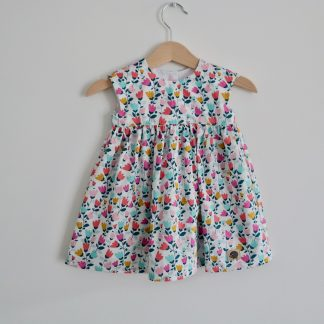 Short sleeved girl's dress made in a white fabric with small pink blue and yellow flowers