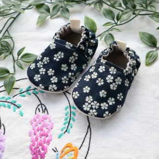 Soft baby pram shoes made in a navy Japanese style cotton fabric with small cream flowers, elasticated at the ankle