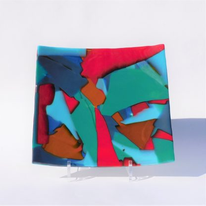 A square multicoloured fused glass platter in a plate stand