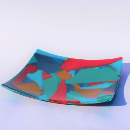 A square multicoloured fused glass platter in a fragmented pattern