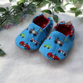 Baby slippers in a bright blue fabric with small racing cars and red stars lining