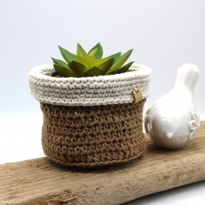 a plant basket made from natural jute with a contrast fold down cuff in ecru cotton.