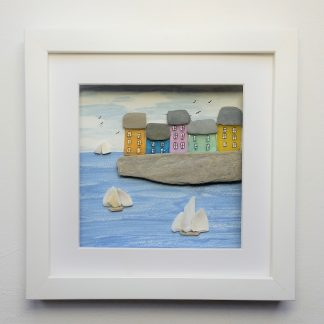 framed picture of colourful sea side cottages and sailing ships