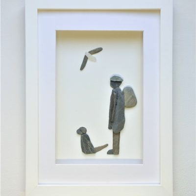 framed pebble art picture of a man and dog
