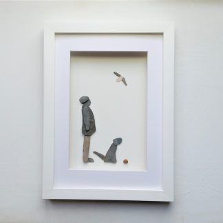 framed pebble picture of a man and his dog