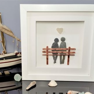 framed picture of a pebble couple sitting on a wooden bench