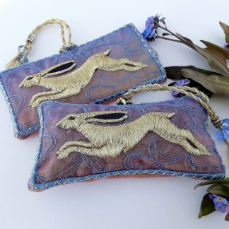 A pair of rectangular shaped lavender bags of misty blue embroidery with a light golden hare featured on this gift item, with gold braids and beads. A few blue Forget me not flowers provides interest on a white background.
