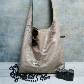Large mushroom or champagne coloured and silver flecked slouchy boho hobo bag pictured with black beads, sunglasses and a camera