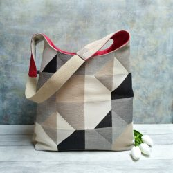 Neutral tones geometric design large hobo bag with red lining pictured with three white tulips