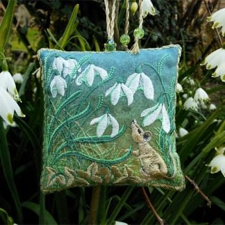 Garden scene of snowdrops with a sqaure embroidered lavender bag in the middle of white Snowdrop flowers and golden mouse on green back ground