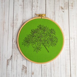 Wildflower seed heads hand stitched in dark green on a bright green background by Sweet Thorn
