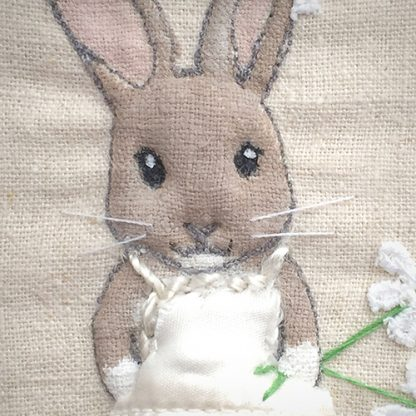 Dressed-up fabric rabbit picture, framed in a tin