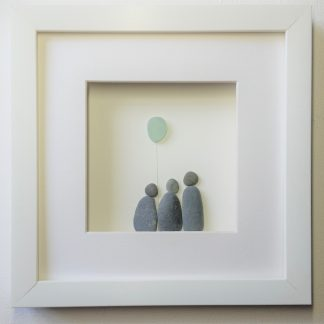 framed pebble art picture of a family of 3 holding a sea glass balloon