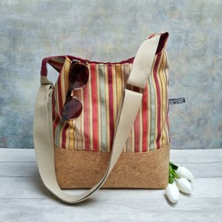 warm tones striped textile and cork fabric bucket bag pictured with three white tulips
