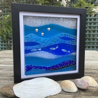 Blue and clear fused glass black box frame featuring waves and dichroic coloured fish