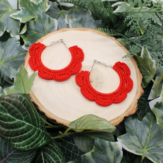 A pair of hoop earrings which have been decorated with crochet in red cotton in the sahpe of petals. They are displayed on a wood slice which in turn is resting on foliage.