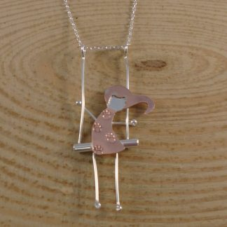 silver and copper girl on a swing necklace