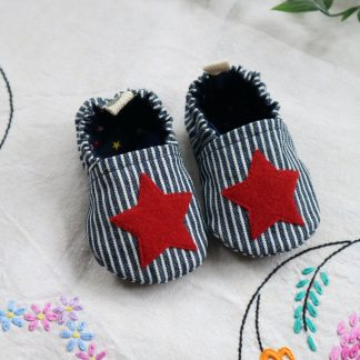 A pair of baby shoes made in a blue striped denim with a red star on the uppers