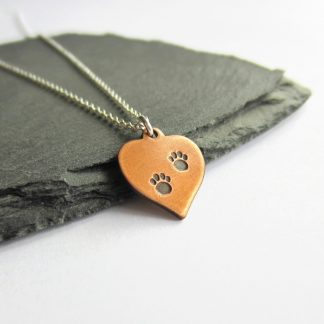 A cute copper heart pendant, hand stamped with tiny paw prints on a sterling silver chain, handmade by The Tiny Tree Frog Jewellery