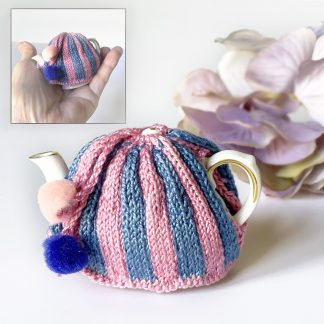 Miniature knitted tea cosy in blue and pink stripes on tiny Coalport teapot