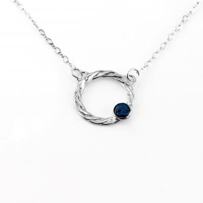 Sterling silver necklace with a woven circle and a blue paua shell cabochon on one side, hung from a sterling silver chain