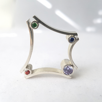 Statement sterling silver ring with cubic zirconias stands on a white surface.