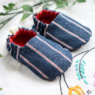 A pair of baby shoes made in blue denim with red stripes & with a red lining
