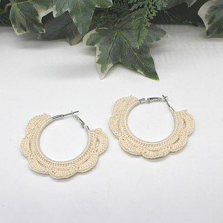 Apair of hoop earrings which have been decorated with cream crochet in the shape of petals. There are six petal shapes on each earring. The earring itself is silver coloured and fastens with a lever back