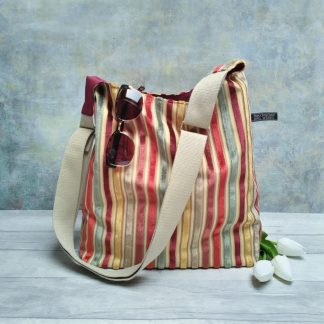 Warm tones striped chenille bucket bag with a khaki strap pictured with white tulips and sunglasses