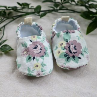 White baby shoes with a lilac & green floral pattern