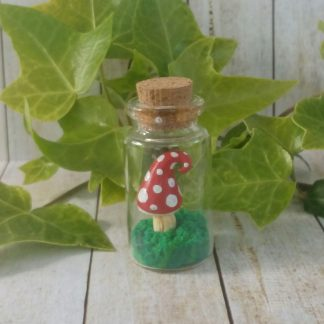 Miniature handmade red spotted toadstool in glass jar