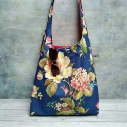 Large floral print large hobo bag with vibrant pink lining pictured with sunglasses