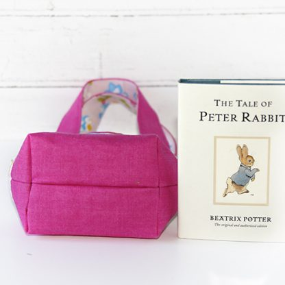 Child's tote bag in pink showing size of base relative to book