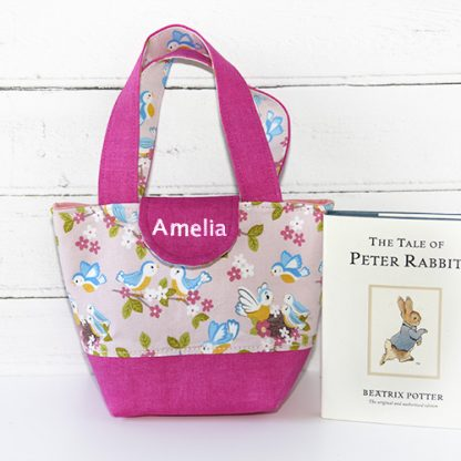 Toddler's tote bag in pink baby birds print showing relative size beside book