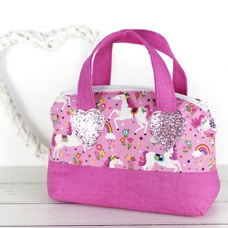 Toy handbag in pink featuring unicorns and rainbows