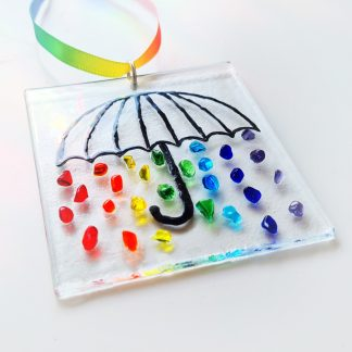 A black umbrella outline with rainbow coloured raindrops falling down