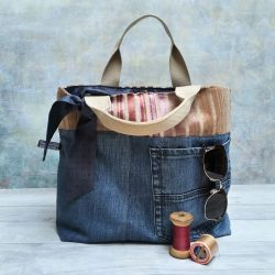 Upcycled denim grab bag with striped chenille trim and navy blue silk lining pictured with vintage cotton reels and sunglasses
