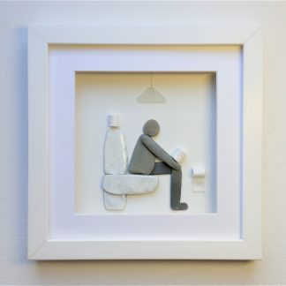 framed pebble art picture featuring a man sitting on a toilet