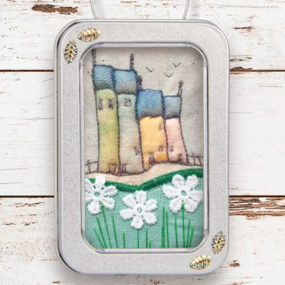 Fabric picture of houses, framed in little tin
