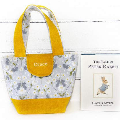 Yellow toy tote bag beside book to show relative size