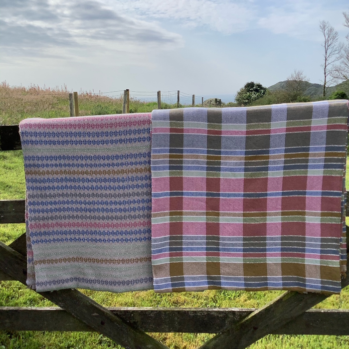 Photo of two pieces of handwoven cloth over a gate