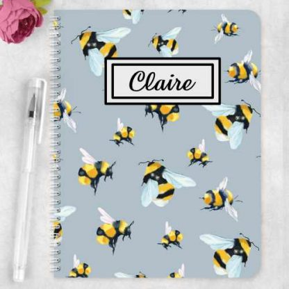 notebook with flying bees and grey background